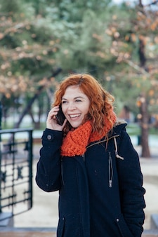 Cheerful woman talking on the phone at winter isolated in the park