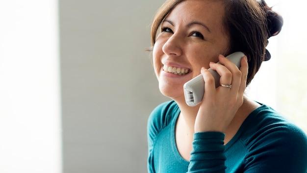 Donna allegra che parla al telefono