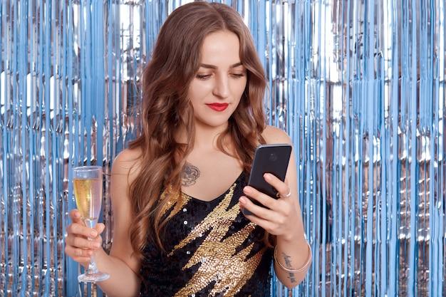 새 해 밤에 쾌활 한 여자 문자 메시지, 검은 드레스에 소녀는 샴페인을 마시고 전화를 들고, 반짝이 반짝이로 장식 된 벽에 집중 보인다.