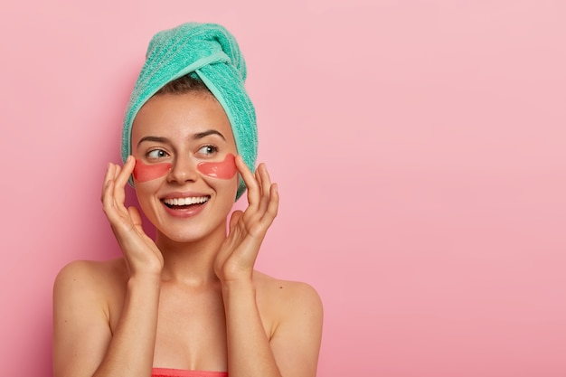 Cheerful woman touches gently face, smiles pleasantly, applies hydrogel patches under eyes, stands naked, has healthy skin