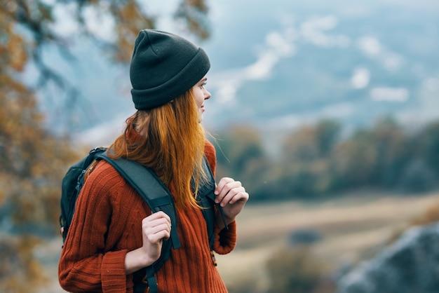 陽気な女性の観光バックパック旅行秋の山々