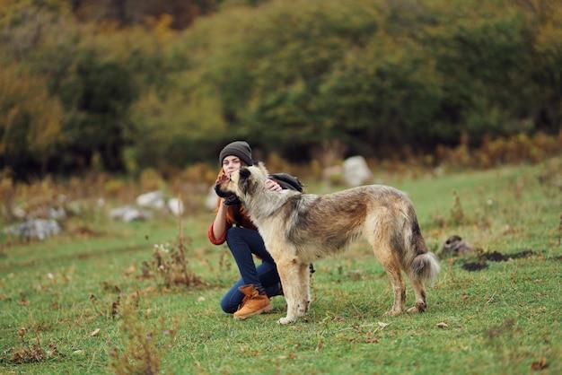 Веселая женщина-турист осенью с собакой путешествия дружбы