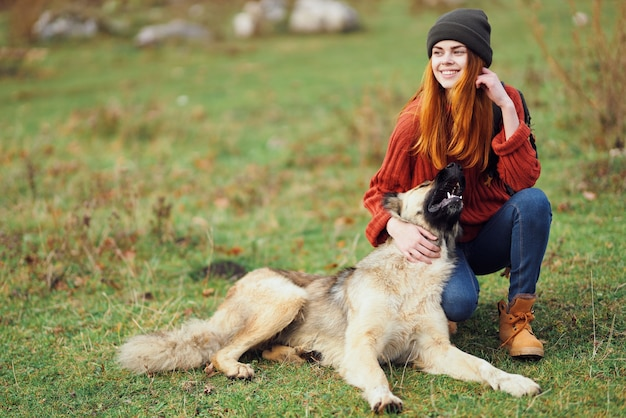 Cheerful woman tourist is playing with a dog in nature on the field