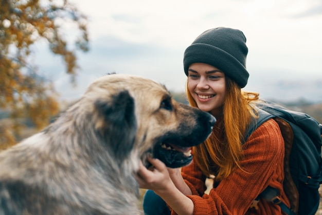 Cheerful woman tourist petting a dog outdoors landscape vacation