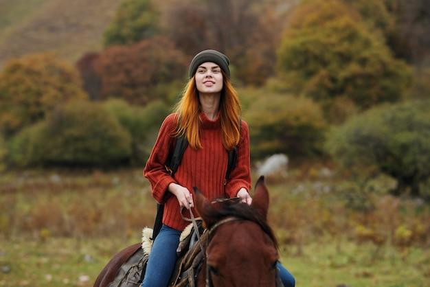 屋外で馬に乗る陽気な女性観光客