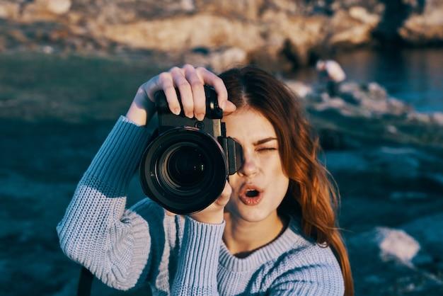 Веселая женщина-турист с аппаратом на природе для профессионалов, путешествующих по горам