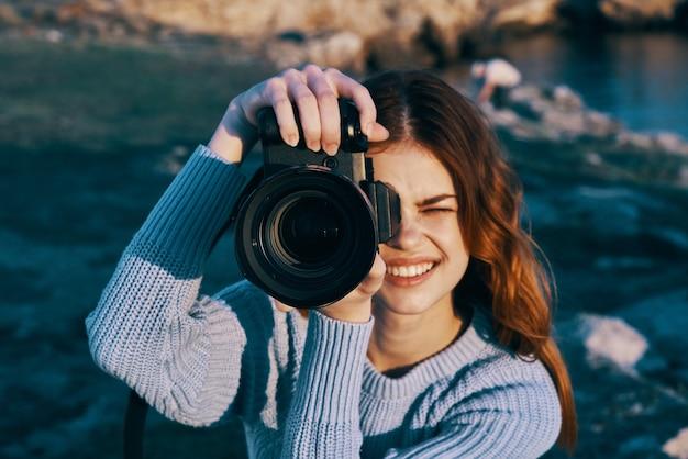 プロの山々のための自然の中で装置を持つ陽気な女性観光客