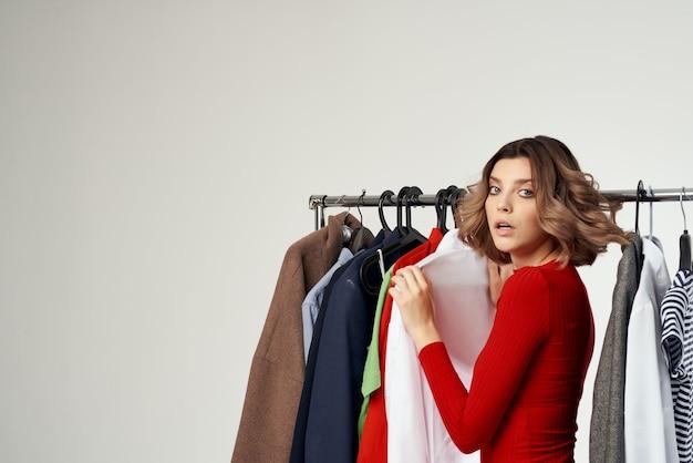 衣料品店の買い物中毒の明るい背景にしようとしている陽気な女性