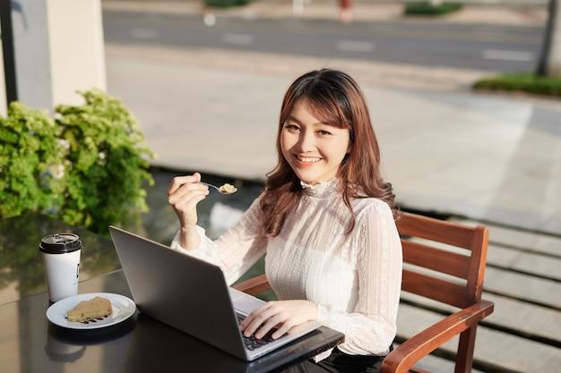 ノートパソコンを使い、カフェでケーキを食べる陽気な女性。