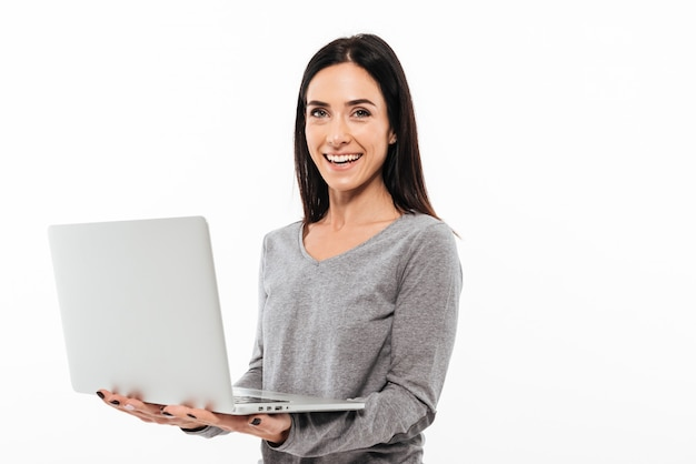 Cheerful woman using laptop computer.