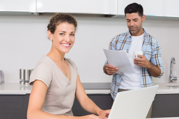 Cheerful woman using laptop while partner reads the newspaper