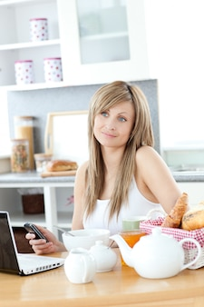 Cheerful woman using a phone and laptop in the kitchen