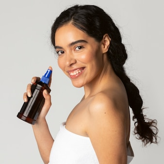 Cheerful woman using a sunscreen spray bottle