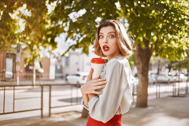 赤いスカートの屋外エンターテイメントを歩く陽気な女性。高品質の写真