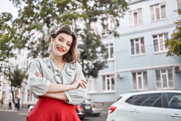 赤いスカートの屋外ライフスタイルを歩く陽気な女性