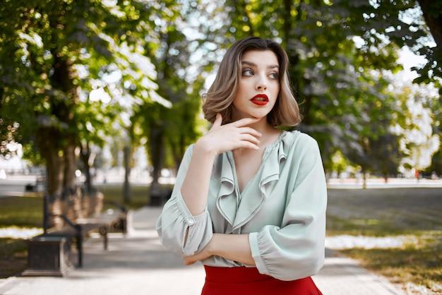 公園の木々のレジャーライフスタイルを歩く陽気な女性