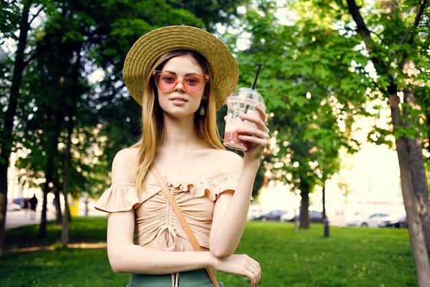 Веселая женщина гуляет в парке на открытом воздухе с напитком образ жизни