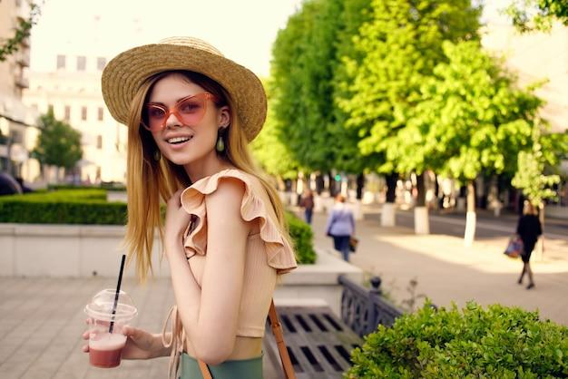 陽気な女性が飲み物の夏と屋外で公園を歩く