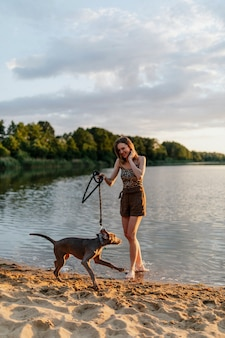 Cheerful woman walks with her weimaraner dog by the lake