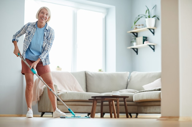 Cheerful woman washing floor at home