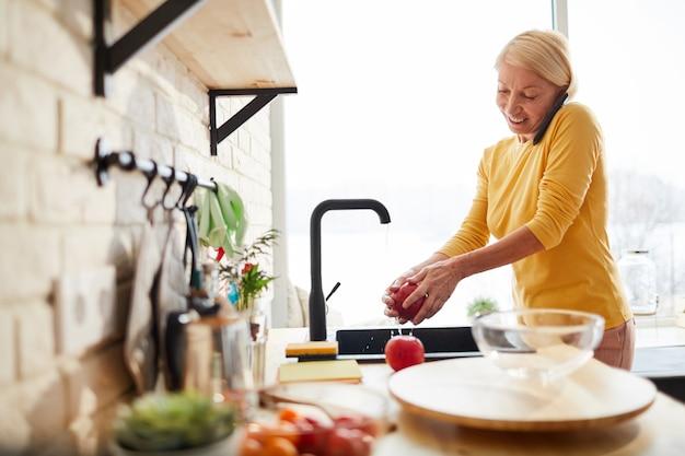 電話で話しながら果物を洗う陽気な女性