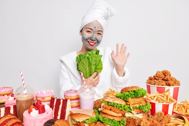 La donna allegra ondeggia il palmo alla telecamera agita la mano e tiene la lattuga romana verde