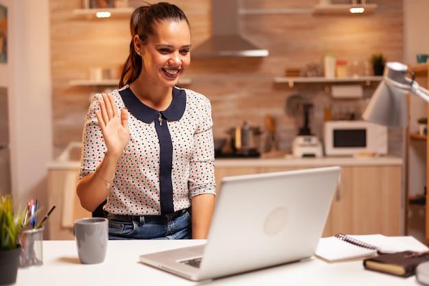 自宅のキッチンから夜遅くまで働いている間、ビデオ通話中に手を振っている陽気な女性。深夜に最新のテクノロジーを使用して、仕事、ビジネス、キャリア、ネットワーク、ライフスタイルのために残業している従業員。