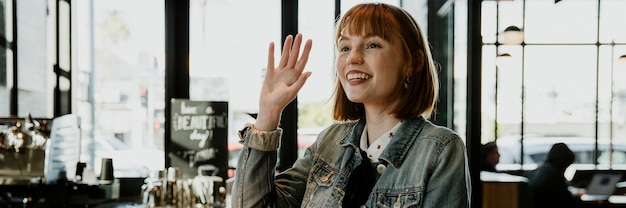 Cheerful woman waving her hand at the cafe