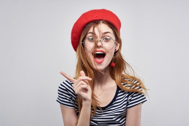 ライフスタイルをポーズする赤い帽子の化粧ファッションを身に着けている陽気な女性。高品質の写真