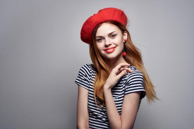孤立した背景ポーズの赤い帽子メイクフランスヨーロッパファッションを身に着けている陽気な女性