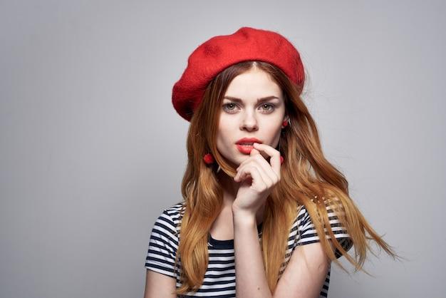 夏のポーズをとって赤い帽子メイクフランスヨーロッパファッションを身に着けている陽気な女性