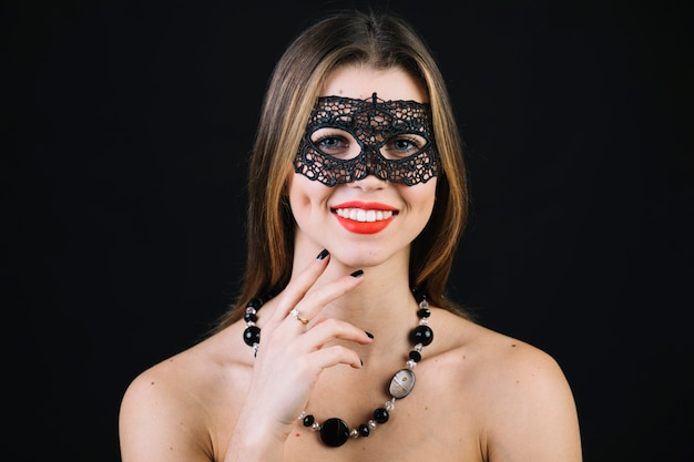 Cheerful woman wearing carnival mask and necklace over black background
