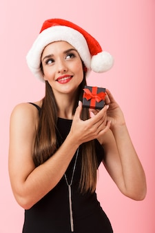 Cheerful woman wearing christmas hat holding a gift box isolated over pink background