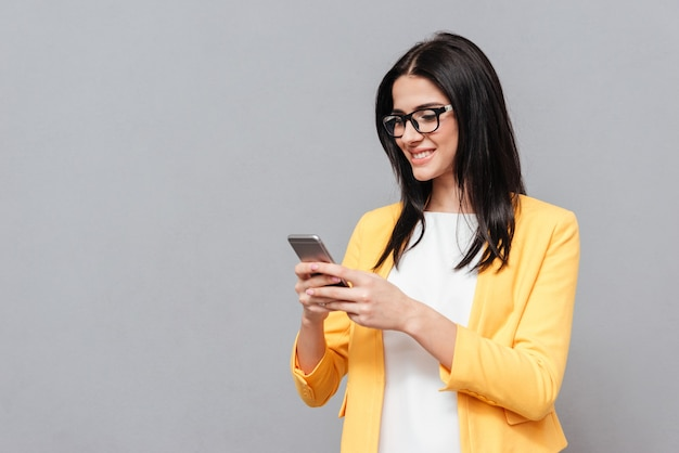 Cheerful woman wearing eyeglasses and dressed in yellow jacket chatting by her phone over grey surface. look at phone.
