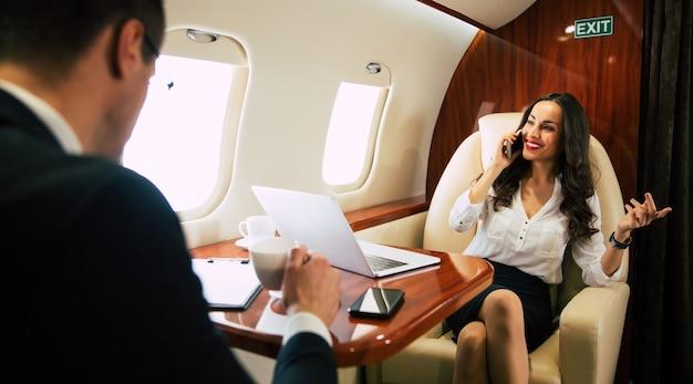 정장 차림과 안경을 쓴 쾌활한 여성이 노트북에 무언가를 입력하고 전화 통화를 하고 동료와 함께 비즈니스 클래스를 비행합니다.