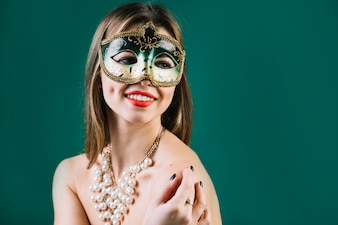 Cheerful woman wearing green carnival mask and necklace