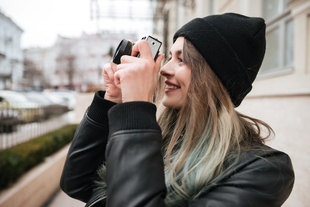Cheerful woman wearing hat holding camera.