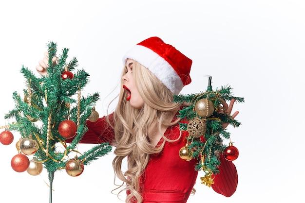サンタクロースの衣装の伝統的な装飾の休日の光の背景を身に着けている陽気な女性