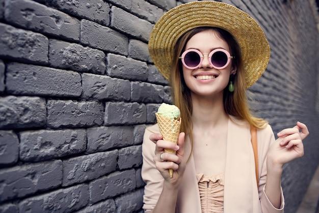 サングラスのレンガの壁の散歩アイスクリームを身に着けている陽気な女性