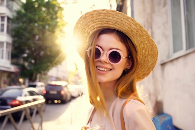屋外でサングラスをかけている陽気な女性は夏を歩きます