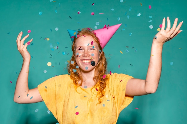Cheerful woman wearing two birthday cones