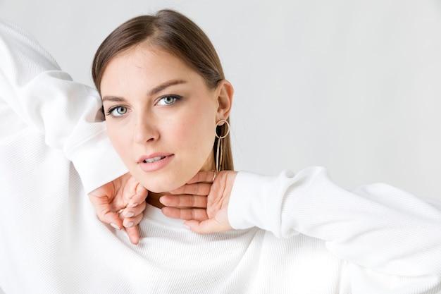 흰색 스웨터를 입고 쾌활한 여자
