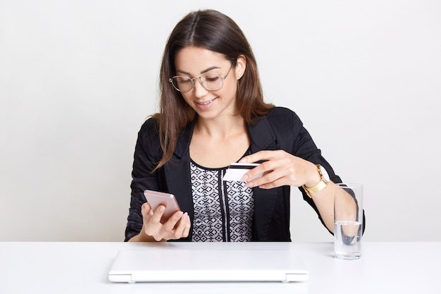 Cheerful woman wears transparent glasses, dressed in black clothes, holds modern cell phone, plastic card, happy to recieve salary, poses on white, drinks water, works remotely