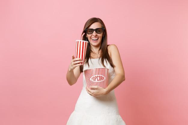 Donna allegra in abito bianco occhiali 3d che guarda film con secchio di popcorn, bicchiere di plastica di soda o cola