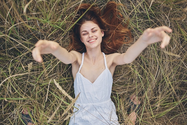 Cheerful woman in a white dress lies on the grass top view rest