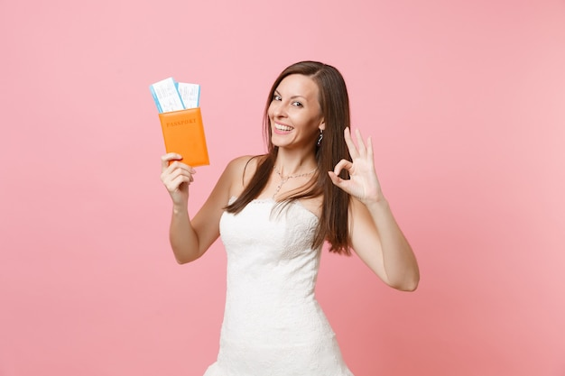 Cheerful woman in white dress showing ok sign, holding passport and boarding pass ticket, going abroad, vacation
