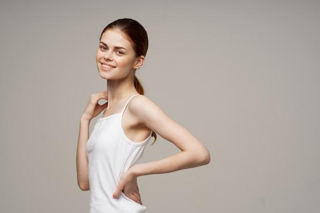 Cheerful woman in white tshirt warmup shoulders health