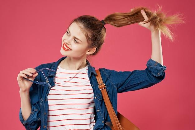 彼女の髪の十代のバックパックの学生を保持しているバックパックを持つ陽気な女性