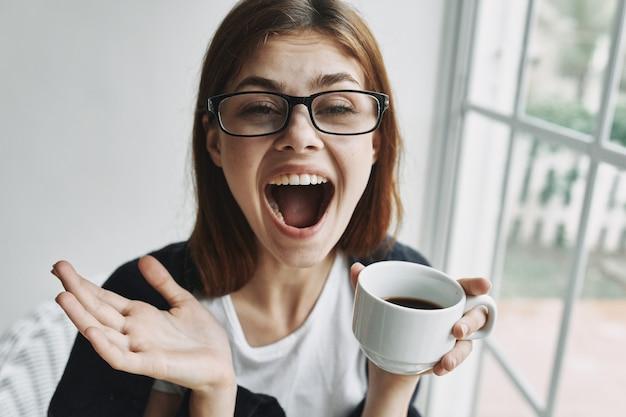 窓の近くで一杯のコーヒーの感情を持つ陽気な女性