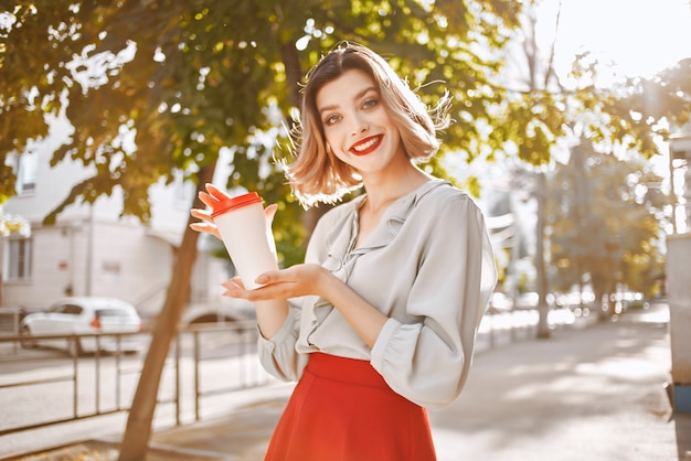 夏に屋外で一杯のコーヒーと陽気な女性
